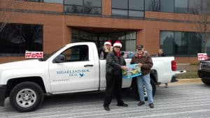 Kevin McKernin, Sugarland Run Board of Directors and Donna McKernin, Community Activities Committee present donation to Toys for Tots.